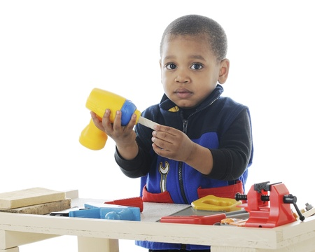 Closeup image of an adorable toddler playing carpenter with plastic tools on a work bench   On a white background