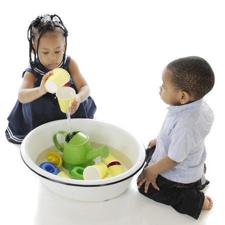 An overhead view of two adorable kis playing with toys in a tub of water   On a white background  Фото со стока