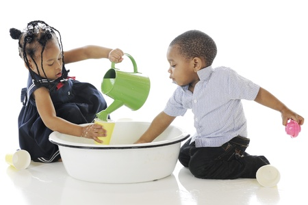 Adorable, young siblings busy in a tub of water and water toys   On a white background   photo