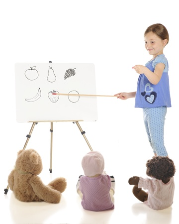 A young elementary girl teaching the names of fruits to her toys   On a white background Stock Photo - 13625029