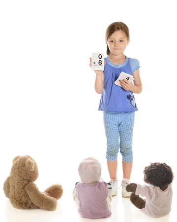 A young elementary girl using flash cards to teach her teddy and dolls to add.  On a white background with plenty of blank space for your text. photo