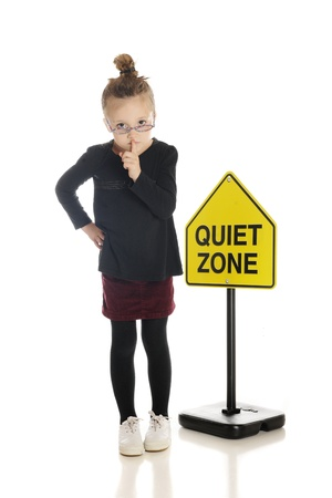 An adorable little girl school teacher or librarian, gesturing to silence the viewer.  She stands in front of a Quiet Zone sign.  On a white background. Stock Photo