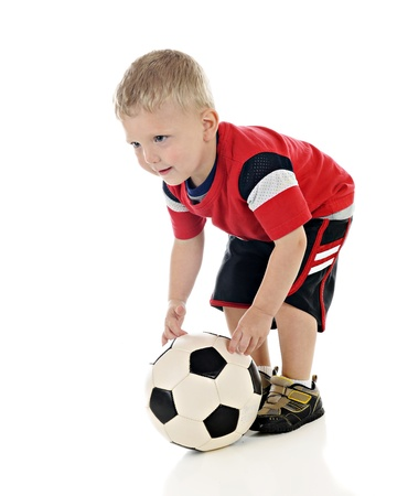 An adorable 2-year-old positioning his soccer ball for a good kick.  On a white background.