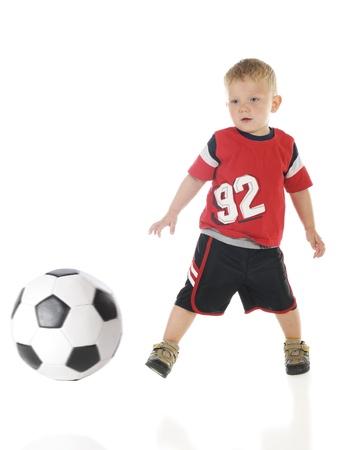 Een twee jaar oud in zijn atletische shirt en korte broek schopt een voetbal bal. Motion blur op de bal. Op een witte achtergrond.