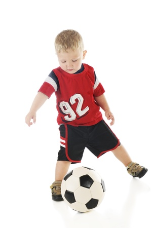 An adorable 2 year-old in his sport shirt and shorts kicking a soccer ball.  On a white background.