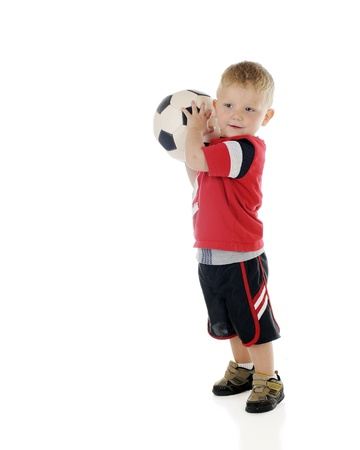 An adorable 2-year-old preparing to toss his soccer ball.  On a white background. Imagens