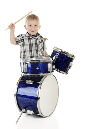 A 2-year-old happily playing a set of shiny blue drums.  On a white background.