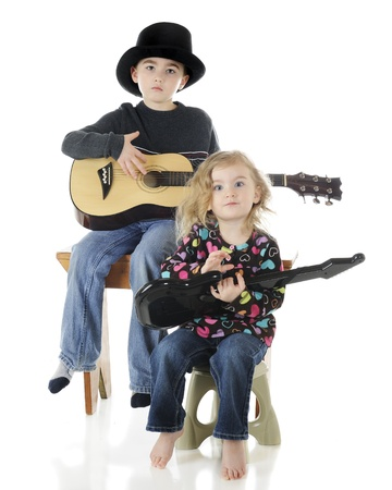 A serious, young elementary boy playing a classical guitar while his preschool sister works on an electric guitar   On a white background  photo