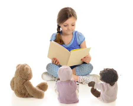 An adorable young  teacher  reading a book to her toy students   On a white background  Stock Photo - 13786952