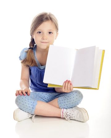 A beautiful young elementary girl sitting cross-legged on the floor while showing the viewer the open pages  left blank for your text  of her book   On a white background  Stock Photo