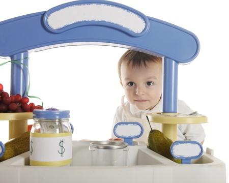 a jar stand: An adorable preschooler looking out from under his fruit stand sign.  The stands signs are left blank for your text.  On a white background.