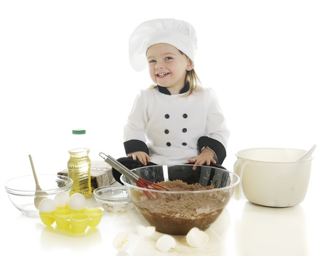 An adorable preschool chef happily making her first cake.  On a white background. photo