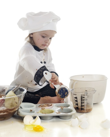 An adorable preschool chef laddeling her batter into a cup cake tin.  On a white background. photo