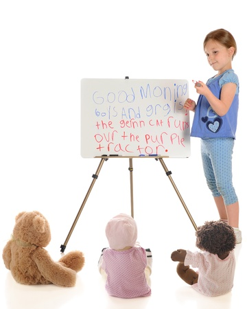 A young elementary girl playing school with her dolls and teddy bear.  On a white background.