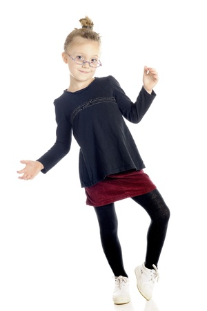 An adorable elementery girl dancing with her hair tied up in a bun and glasses perched low on her nose   On a white background Stock Photo - 13829127