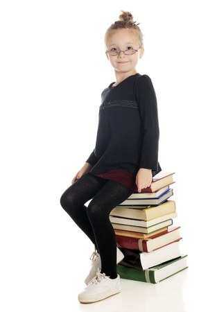 An adorable girl playing  teacher librarian  sitting on a tall stack of books   On a white background  photo