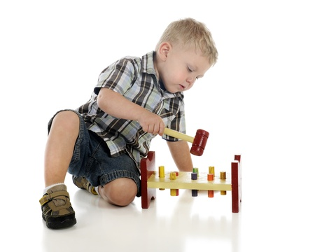 A young preschooler playing with a ped and hammer toy   Motion blur on the hammer   On a white background