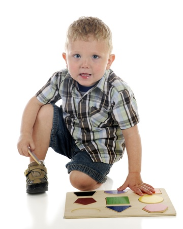 A young preschooler ready to place the last piece of his puzzle of shapes   On a white background