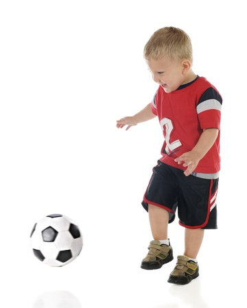 An adorable 2-year-old prepared to kick an approaching soccer ball   Motion blur on ball and child