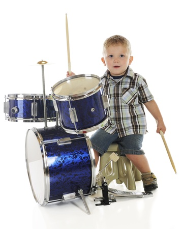 A young preschooler looking at the viewer as he plays on a drum set   On a white background