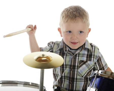 Closeup image of a young preschooler happily playing the drums   On a white background  photo