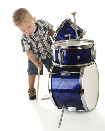 An adorable preschooler bending over a drum set to beat the base drum with a drumstick   On a white background