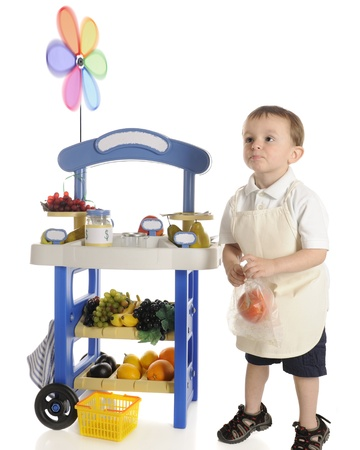 An adorable preschool fruit  vendor  standing by his fruit stand with an apple in a plastic bag, looking out towards customers  not visible    Motion blur on the pinwheel,  The stand photo