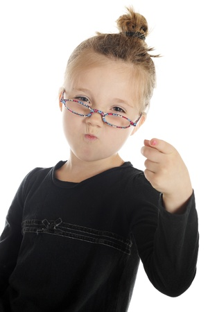 puckered: Closeup of an adorable elementary girl pointing directly at the viewer   She has her hair in a bun, glasses slipping down her nose and sour look on her face   On a white background