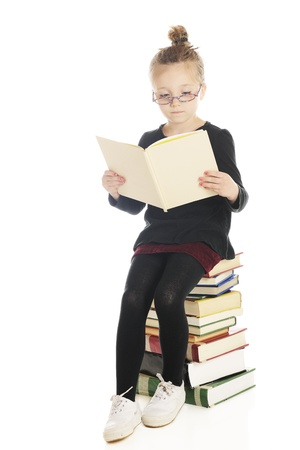 An adorable elementary reader sitting on a tall stack of books with low colorful glasses and her hair in a bun   On a whtie background  Stock Photo