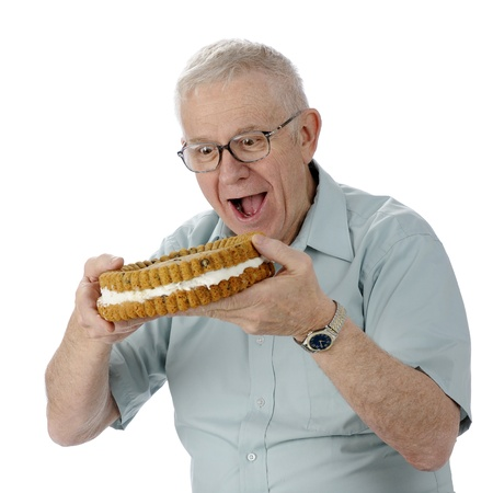 eager: A senior man eagerly ready to bite into a giant, cream-filled cookie   On a white background