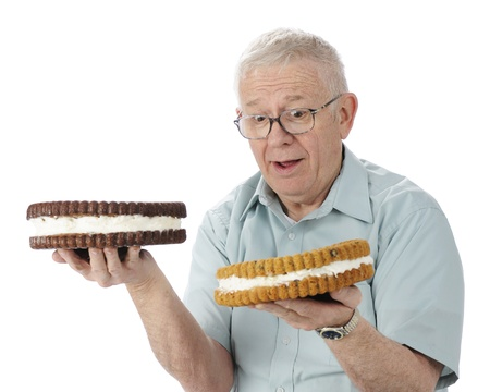 A perplexed senior man trying to decide which giant cookie he Stock Photo - 13900103
