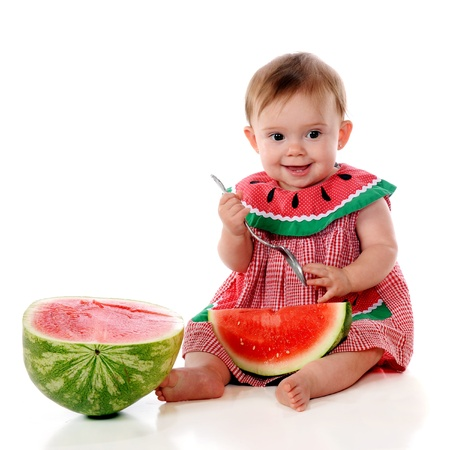 An adorable baby in a watermelon sundress digging into her first watermelon    photo