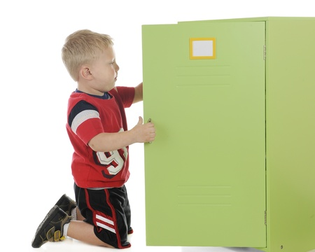 A young preschooler-athlete dressed for sports and into his locker   The locker label left blank and plenty of space on the locker door for your text   On a white background