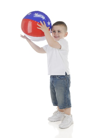 A young preschooler happily catching a patriotic American beach ball   On a white background  Stock Photo - 13944315