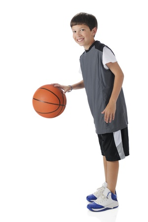 A preteen athlete dribbling his basketball   Motion blur on ball   On a white background