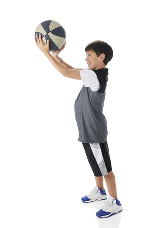 A preteen boy preparing for a standing basketball shot   On a white background  Stock Photo