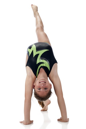 girl kick: Front view of a pretty elementary gymnist kicking one leg while doing a  bridge    On a white background  Stock Photo