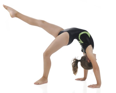 arched: A side view of an elementary gymnist making a  bridge  and kicks out with one leg  On a white background