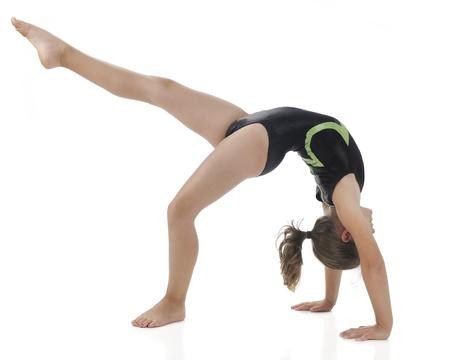 gymnastik: Eine Seitenansicht eines elementaren Gymnist eine Br�cke und tritt heraus mit einem Bein auf einem wei�en Hintergrund Lizenzfreie Bilder
