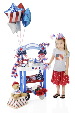 An adorable preschooler longingly standing by her Fourth of July vendor stand   The stand photo