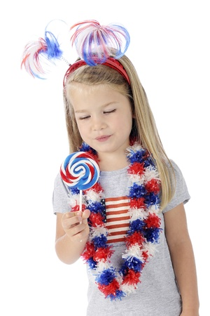 leis: An adorable preschooler dressed to celebrate Independence Day, looking longingly at the red, white and blue swirrled lollipop she holds   On a white background