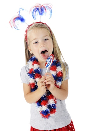 An adorable preschooler celebrating the Fourth of July with her accessories and licking a red, white and blue lollipop   On a white background  Foto de archivo