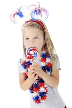 An adorable preschooler celebrating the Fourth of July with red, white and blue accessories, including the lollipop she Stock Photo - 13963654