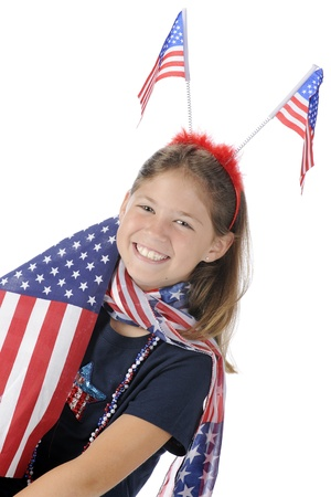 A pretty elementary girl showing her american pride with flags and accessories in stars and stripes   On a white background  Stock Photo - 13963655
