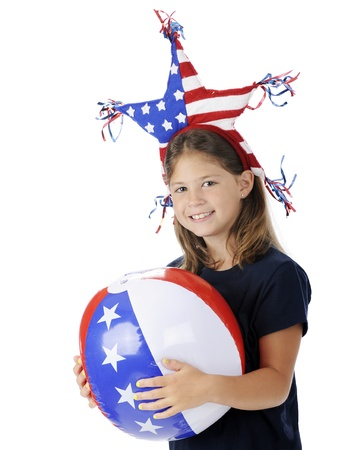 A pretty elementary girl celebrating Independence Day with a patriotic headband and beach ball   On a white background Stock Photo - 13963643