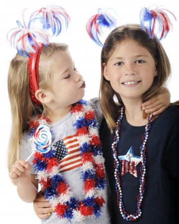 An adorable preschooler giving her sister a kiss with lips turned blue from her lollipop   Both girls wear American patriot accessories   On a white background  Stock Photo - 13963661