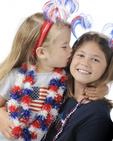 A pretty preschool girl kissing her elementary sister   Both are dressed for Independence Day Celebrations   On a white background  photo