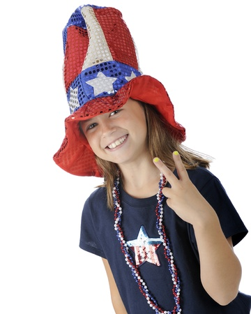 fourth of july: A pretty elementary girl in a tall, sparkly Uncle Sam hat gesturing  victory  with her fingers   On a white background  Stock Photo