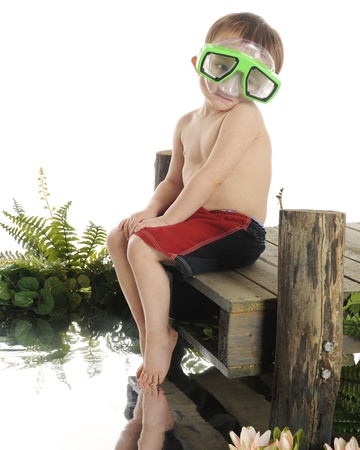 A sad preschooler sitting on a dock, sadly wearing an oversized swim mask,  his toes dragging in the water.  On a white background. photo