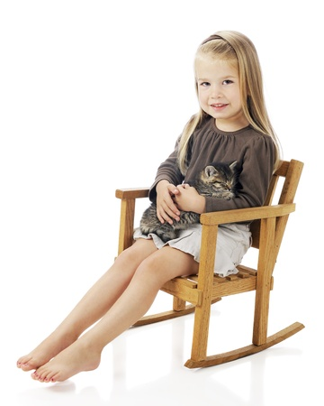 A pretty, barefoot preschooler in a rocking chair with a kitty in her lap.  On a white background. Stock Photo